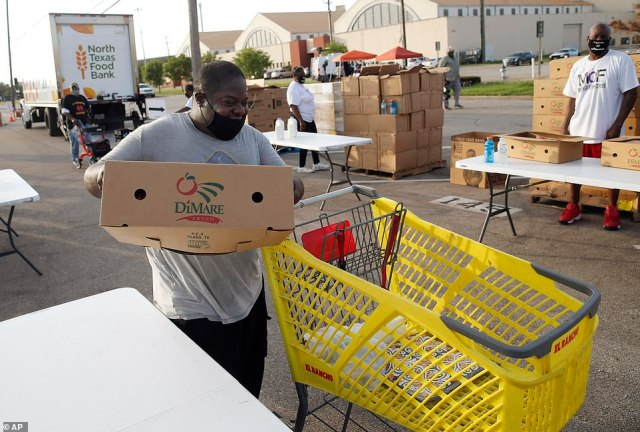 Toby Overstreet of Dallas grabs a box of food as he makes his way through the walk-up line of the North Teas Food Bank