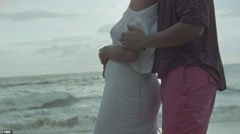 Baby number three! In the video, John tenderly holds his wife as she rests her hands upon her torso, revealing her pregnancy