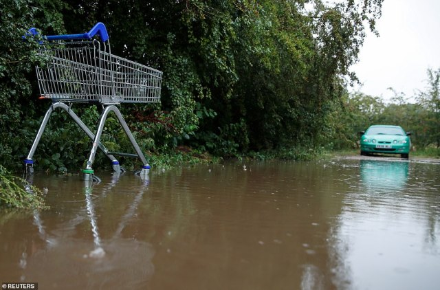 A shopping cart is seen in a flooded car park after heavy rain, in Hertford, Hertfordshire, as a car stops before entering the pool yesterday