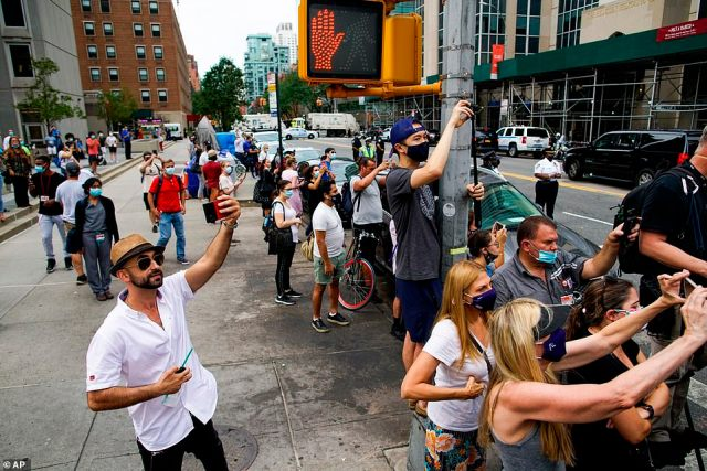 People try to take pictures of the motorcade with President Donald Trump as he arrives to the New York-Presbyterian Hospital