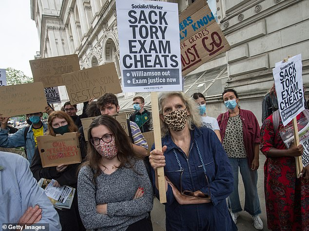 Pictured: Students and parents hold a placards on Whitehall outside Downing Street in London on Friday, afternearly 40 per cent of results were downgraded by the computer model deployed when exams had to be cancelled due to the coronavirus crisis, affecting disadvantaged areas most