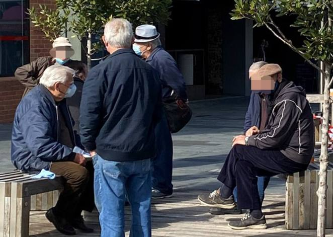 Another group of elderly men are seen sitting down in the sun on Saturday as they enjoyed a bright day in Melbourne