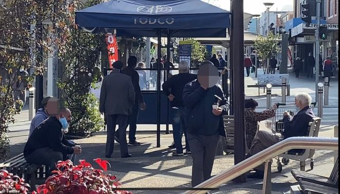 Elderly men are seen sitting near a coffee stand and wearing face masks on Saturday. Victoria is currently in a state of disaster as COVID-19 cases surge