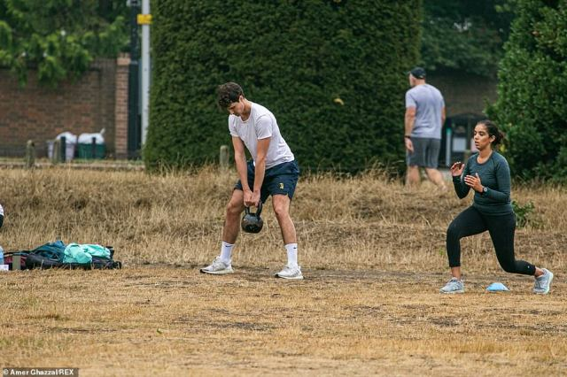 Thunderstorms and torrential downpours are set to sweep across the UK in a three-day deluge. Pictured: People working out on the dried-out grass in Wimbledon Common