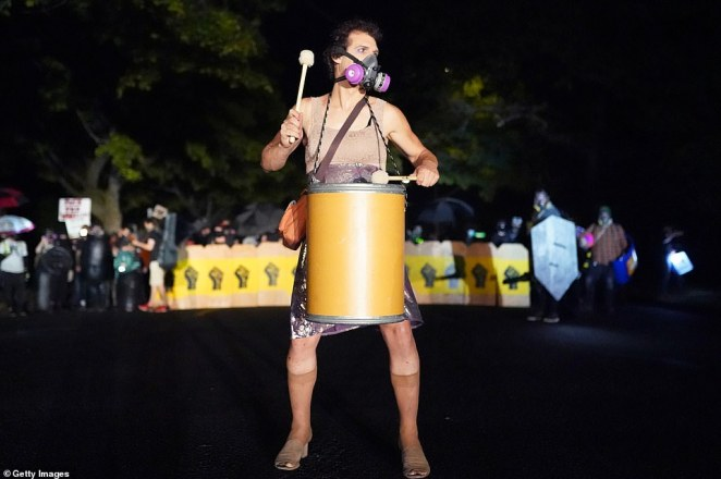 Tabitha Poppins, a regular attendee of Portland's nightly protests, plays a drum while roughly 400 people faced off with police