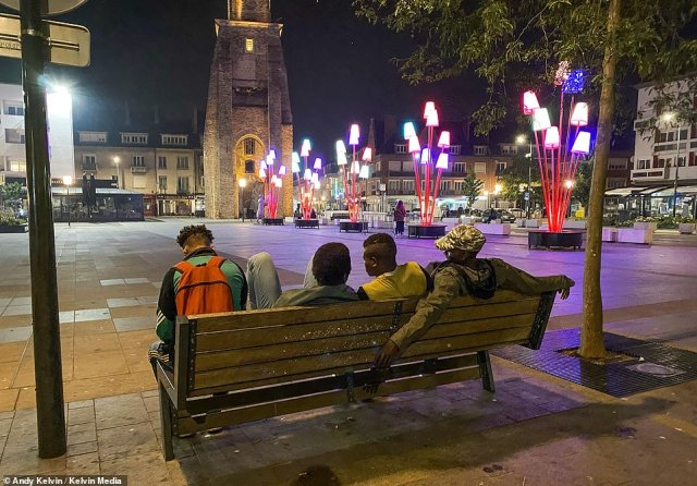 Migrants are seen sitting in Calais town square in the late evening.The number of successful Channel crossings peaked two weeks ago with a record of 235 on just one day