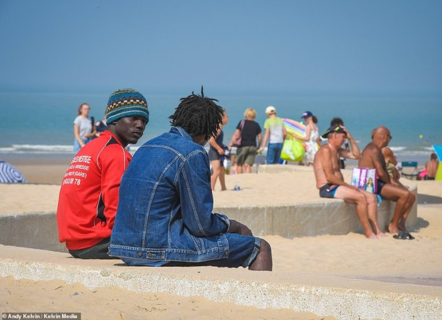 Under the hot sun in northern France, the long beach lined by dunes and dotted with bright parasols is crowded with holidaymakers. Sitting on a low wall above them are two young Africans, one with an incongruous woollen hat pulled over his ears