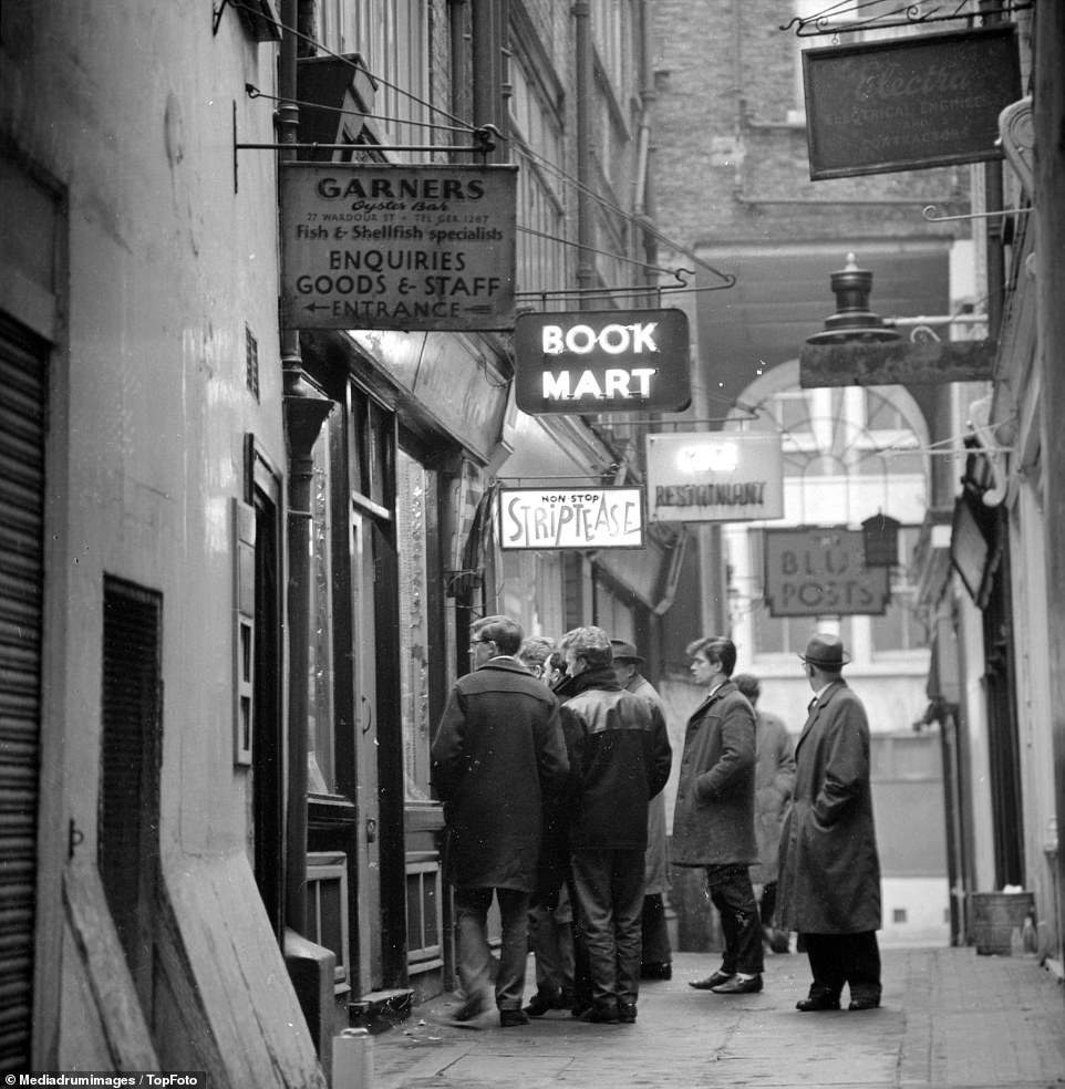A group of men stand outside an entrance to a strip club, with the building signposted 'non stop striptease', in a Soho alleyway in February 1962. London's Soho area was a hotspot for the UK's underworld in the mid-twentieth century