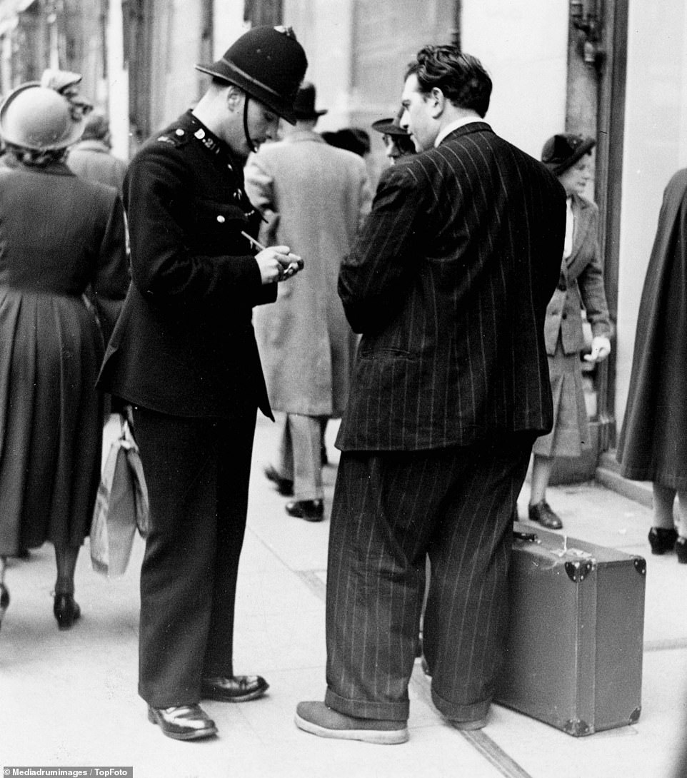 A spiv selling nylons on the pavement in Oxford Street is caught by police, with an officer seen appearing to fine him. Petty criminals, known as spivs, achieved notoriety in the 1950s following the end of the Second World War