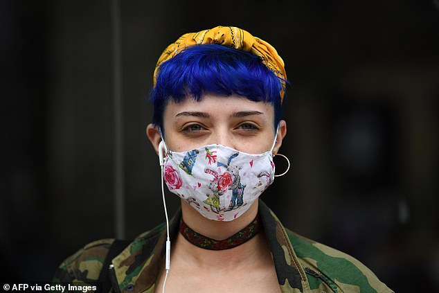 Coughing or sneezing without a mask exposes bystanders to 10,000 times more droplets, a study has found, supporting their use during the Covid-19 pandemic. Pictured: A shopper wearing a mask in Sheffield, south Yorkshire, on July 24