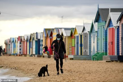 A person wearing a face mask walks their dog along Brighton Beach in Melbourne amid stage four coronavirus restrictions on Thursday