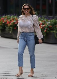 Kelly Brook displays her iconic curves in a sheer gingham blouse and cropped jeans