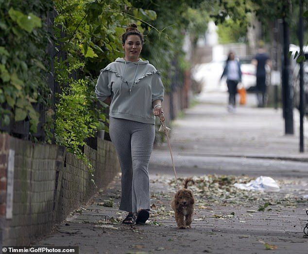 Casually-clad: The television personality appeared in high spirits as she took her beloved dog out