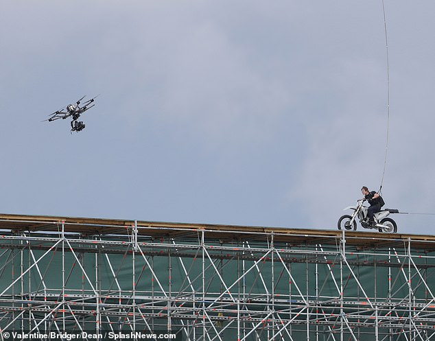 Cruise is pictured exiting the edge of the 650-foot ramp, as a drone films him in an estimated £ 2million stunt sequence - one of the most expensive ever made in Britain