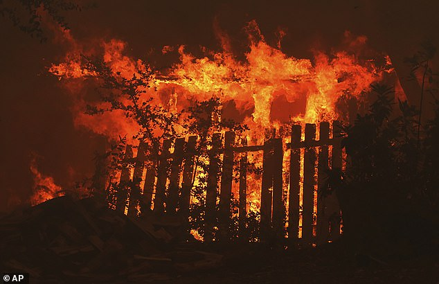 A home is engulfed in flames along Empire Grade Road in the Santa Cruz Mountains community of Bonny Doon near Santa Cruz. The state relies on the prison population to make up a staggering 43 percent of its fire crews