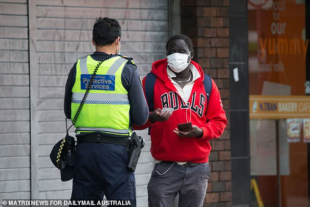 A policeman talks to a man wearing a face mask on Chapel Street in Melbourne city center on Monday