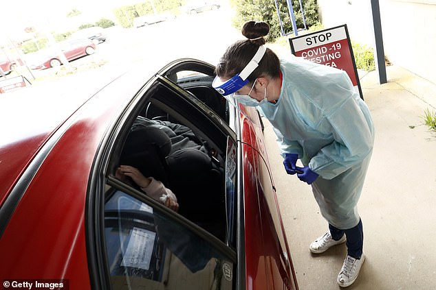 A health worker takes a COVID-19 test at a drive-thru clinic in Ballarat, Victoria on Friday