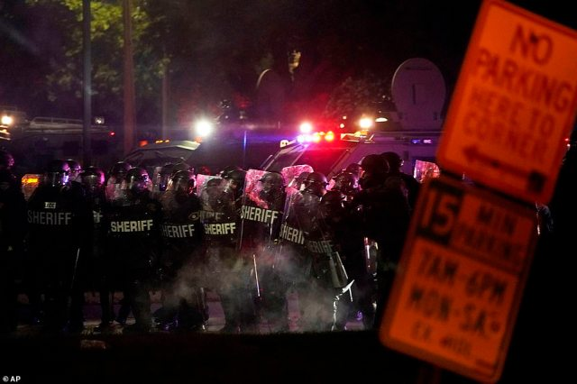 Police in riot gear clear a park during clashes with protesters outside the Kenosha County Courthouse late Tuesday, Aug. 25, 2020, in Kenosha, Wis