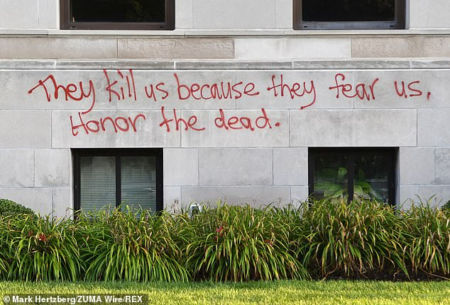 'They kills us because they fear us, honor the dead', a scrawl of graffiti reads on the wall of the Kenosha County Court House