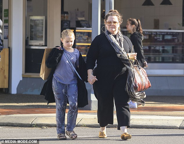 Family time: Melissa held onto her younger daughter Georgette's hand as they crossed the road