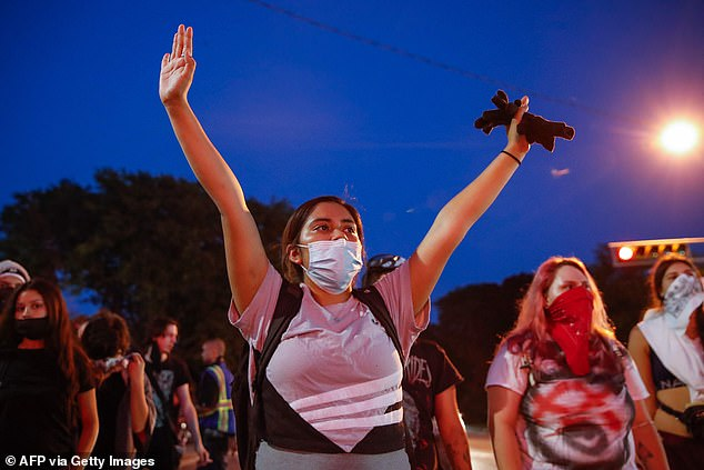A protester holds up her hands during a demonstration against the shooting of Jacob Blake in Kenosha on Wednesday evening, marking a fourth evening of walk outs demanding justice