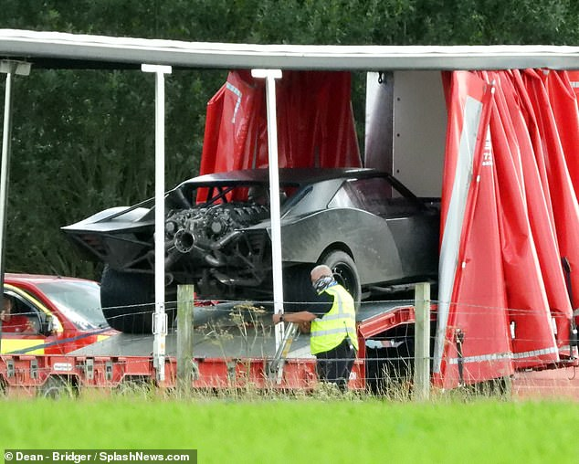 New ride: Crew were seen taking two cars that had been decked out to resemble the Caped Crusader's batmobile out of a van