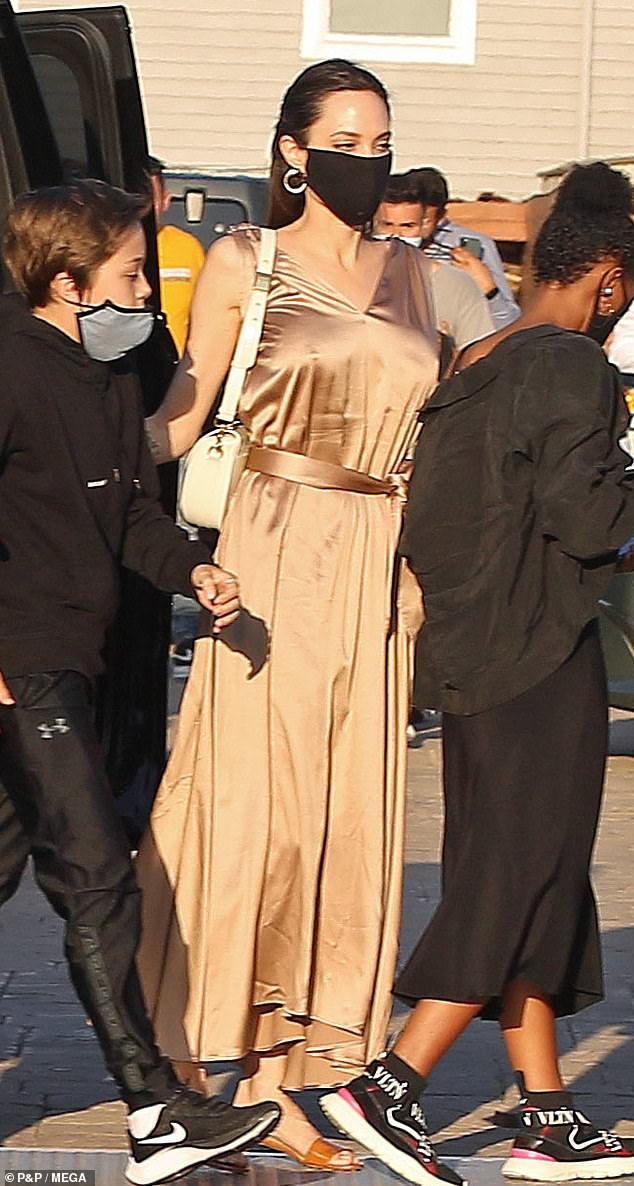 Masked: Angelina was sure to wear a reusable black face mask when going to the restaurant to comply with local and state COVID-19 regulations, all of her children also wore masks