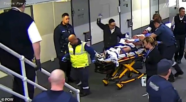 Pictured is the victim being moved on a stretcher by prison and medical staff after the attack. The carnage is believed to be linked to the violent Prisoners of War gang