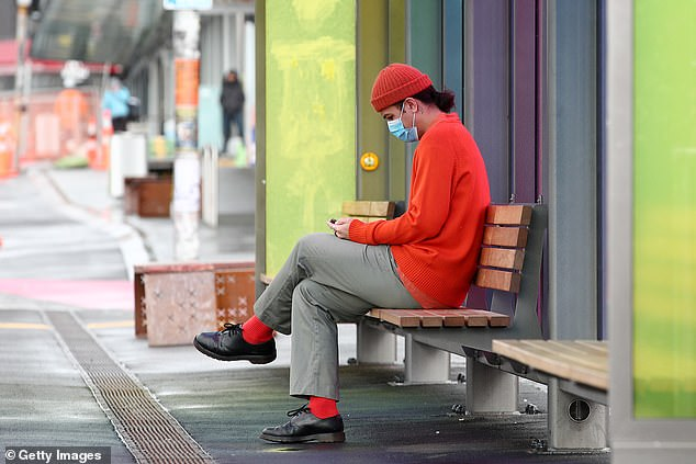A person waits for a bus at a Karangahape Rd bus stop in Auckland after Ms Ardern made face coverings mandatory on public transport