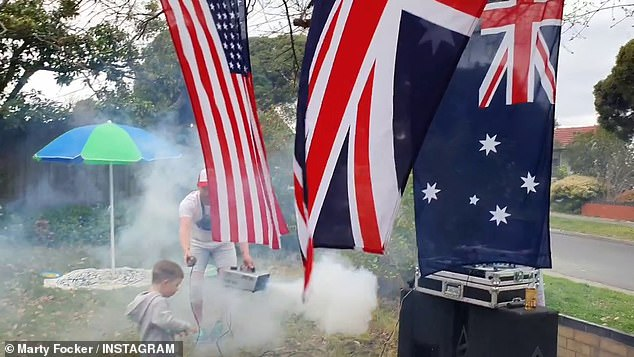 The neighbour blows smoke around the front yard which was decorated with Australian, British, and American flags