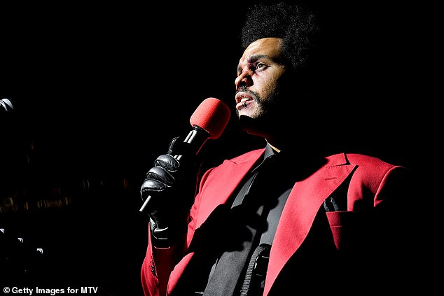 Seeing red: The Weeknd was dressed in a scarlet blazer with peak over a black shirt and matching tie and black trousers