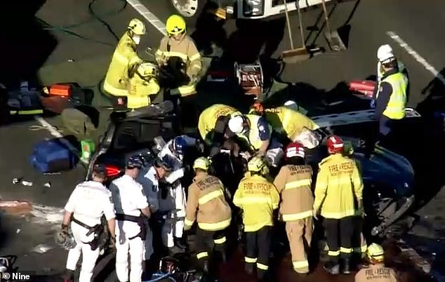 Fire crews and paramedics surround a car involved in a fatal crash in Sydney on Thursday, a woman in her 40s was trapped inside for up to two hours