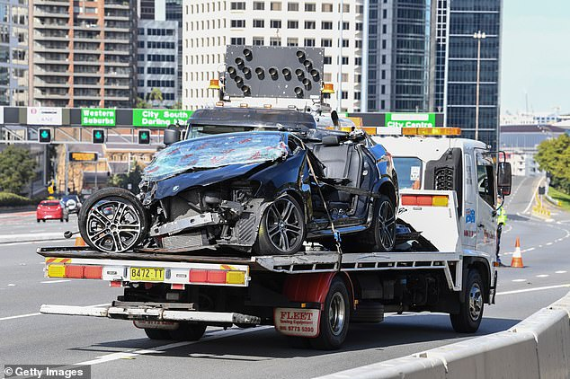 The wrecked BMW (pictured), which had its roof completely torn off, was later taken away on a truck after police had finished investigating the crash scene