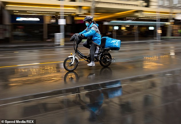 Fresh figures released by AlphaBeta and leading credit bureau illion showed that spending on food deliveries have skyrocketed during coronavirus lockdown. Pictured: A delivery driver is seen in Melbourne on August 14