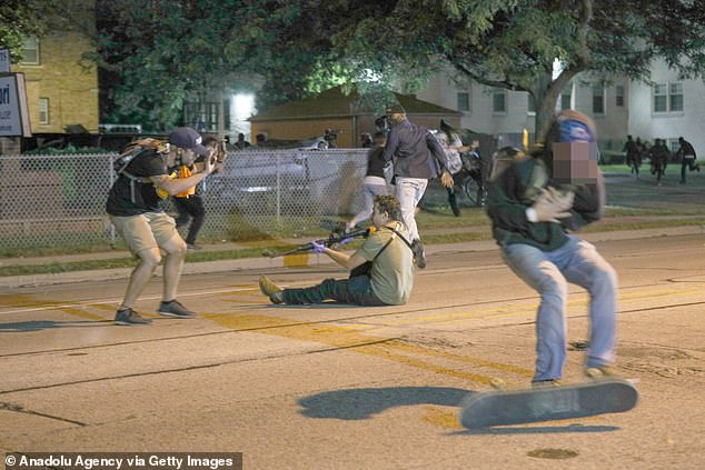 Huber stumbled away from the gunman clutching his chest (right) as another man appeared to put his hands up in front of the shooter