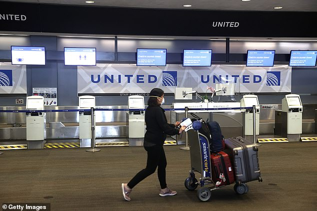 Airlines have seen a dramatic drop in passengers since the pandemic lockdowns began. A passenger pushes her luggage past shuttered United kiosks in San Francisco on July 8