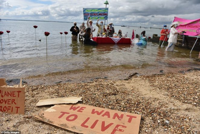 Posters which were scattered on the beach blazoned warnings such as 'we want to live', 'planet over profit' and 'act now'