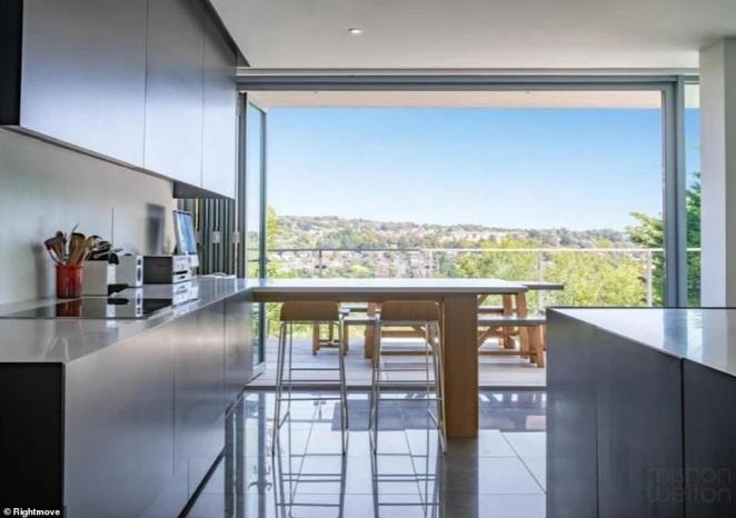 The kitchen is complete with wifi-enabled double ovens and sleek countertops, as well as a stunning view out to the East Sussex countryside from a wooden breakfast bar with glass windows that open completely