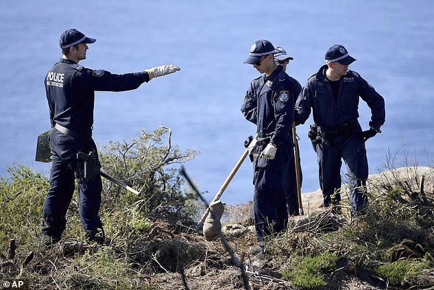 Police conduct a search of a headland on May 12 after an arrest was made in connection with Scott's death
