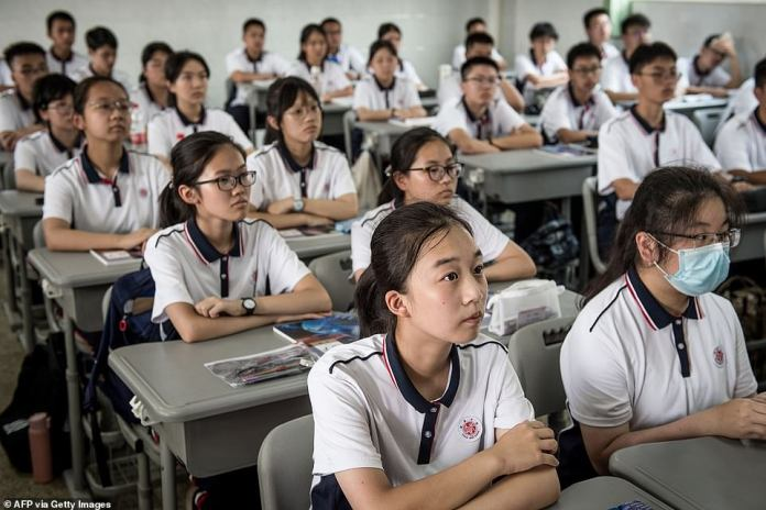 Students are seen attending a class at Wuhan High School on the first day of the new semester in Wuhan