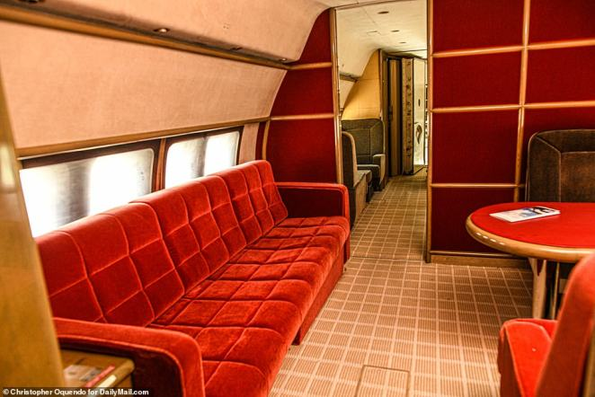 DailyMail.com understands that the records are out of date, however, and that it's changed hands several times since 2016. Pictured: The red garish couch in the middle of the plane with an exectutive table and chairs