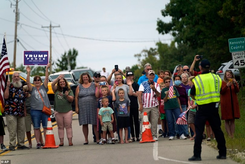 People line up, including some with American flags and Trump signs, to see the president's motorcade as it arrives in Kenosha, Wisconsin
