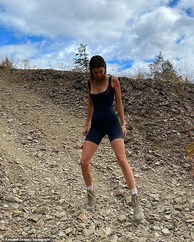 Going down: The 24-year-old model got an action shot, seen steadying herself while going down a rocky trail