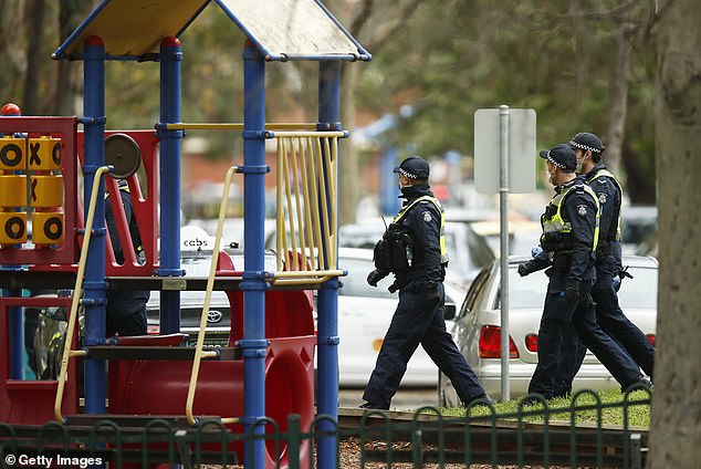 Police patrol a playground in Melbourne in July. Children are still unable to use them across Melbourne with fear of fines and arrest