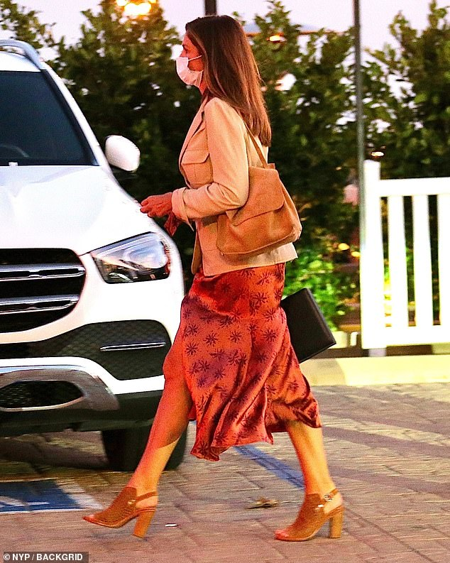 Decked out:She accessorized with a brown suede bag slung over one shoulder while she carried a slim black case in her other hand