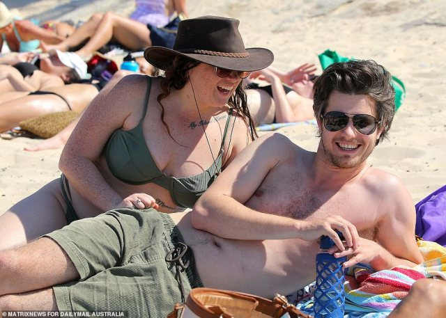 Alex Hale, 29, and Shona Davidson, 27, have a laugh as they enjoy the beach with their friends on Thursday afternoon