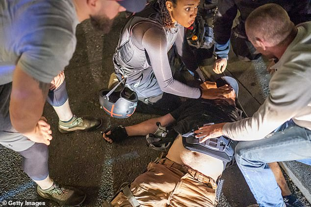 Street medics and protesters help to treat Danielson, who was shot near a Pro-Trump rally