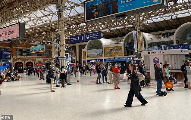 Rail passengers arrive at Victoria Station in London during the morning rush hour yesterday