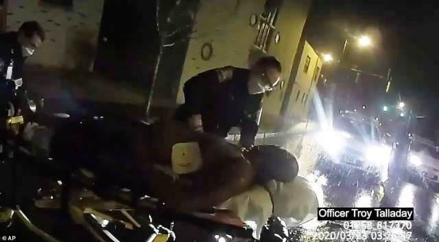 The medics continue performing CPR on Prude before he's loaded into an ambulance, some 11 minutes after he first encountered police