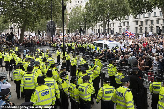 Demonstrators in the Unite for Freedom rally - which started at noon in the capital - called for an 'end to Government lies' and the restoration of all freedoms as they marched past Downing Street towards the Houses of Parliament (police pictured at the scene)